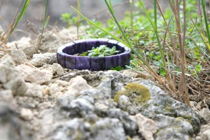 deep purple charoite resting on a rock with some grass