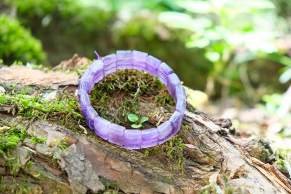 Beautiful dreamy amethyst square bead bracelet on a mossy tree out in nature