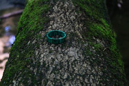 Cool green malachite resting on a tree trunk over a river
