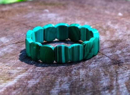 Beautiful green malachite bracelet on a tree trunk